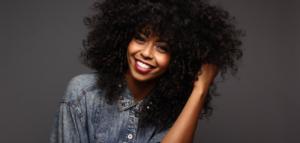 jeune femme afro avec belle chevelure frisés hydratée et nourrie grâce à un soin profond