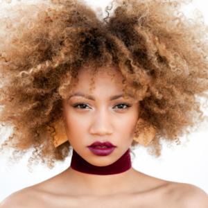 femme afro avec cheveux bouclés décolorés secs et cassants à cause des colorations chimiques