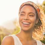jeune femme afro métissée portant un foulard pour coiffer ses cheveux frisés